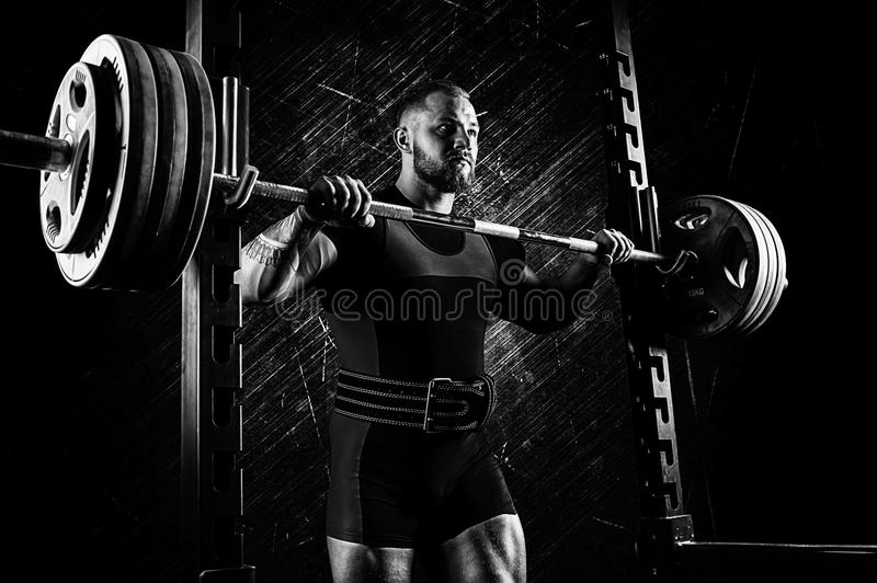 Professional athlete prepares to squat with a barbell. Mixed media royalty free stock photo