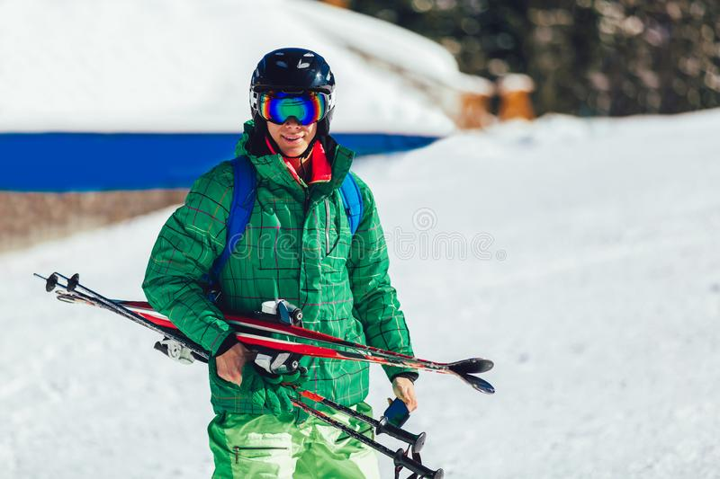 Professional athlete skier in an green jacket wearing a black mask and holding skis. Portrait of a professional athlete skier in an green jacket wearing a black stock images