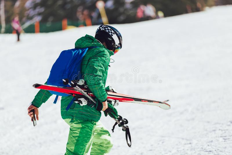 Professional athlete skier in an green jacket wearing a black mask and holding skis. Portrait of a professional athlete skier in an green jacket wearing a black stock image