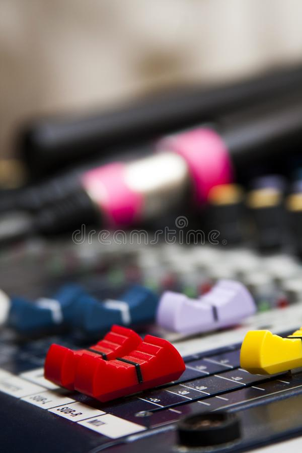Professional audio mixer with colorful faders, microphones lying in the blurred background. Professional audio mixer with colorful faders, microphones laying in royalty free stock photography