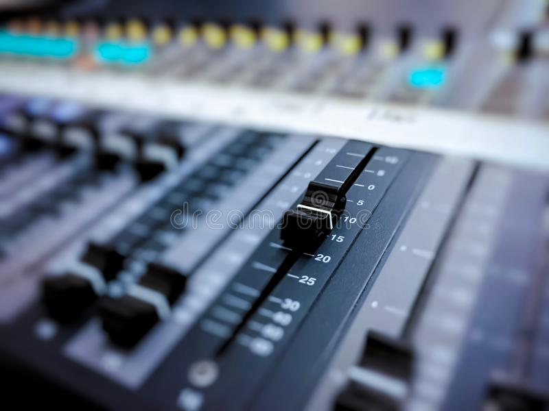 Professional audio mixer console with black knobs to equalize sounds. Audio recording studio tool. Music and entertainment concept stock photography