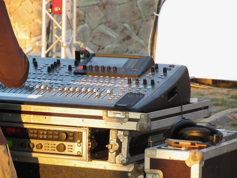 Professional audio mixing console with faders and adjusting knobs for party outdoor at sunset.  royalty free stock photography