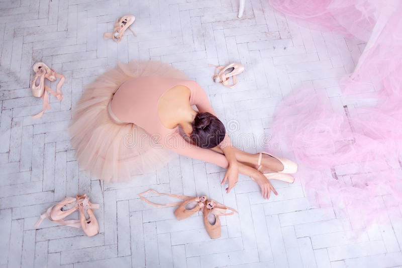 Professional ballet dancer resting after the performance. Professional ballerina resting after the performance against the backdrop of pink veil and pointes royalty free stock photo