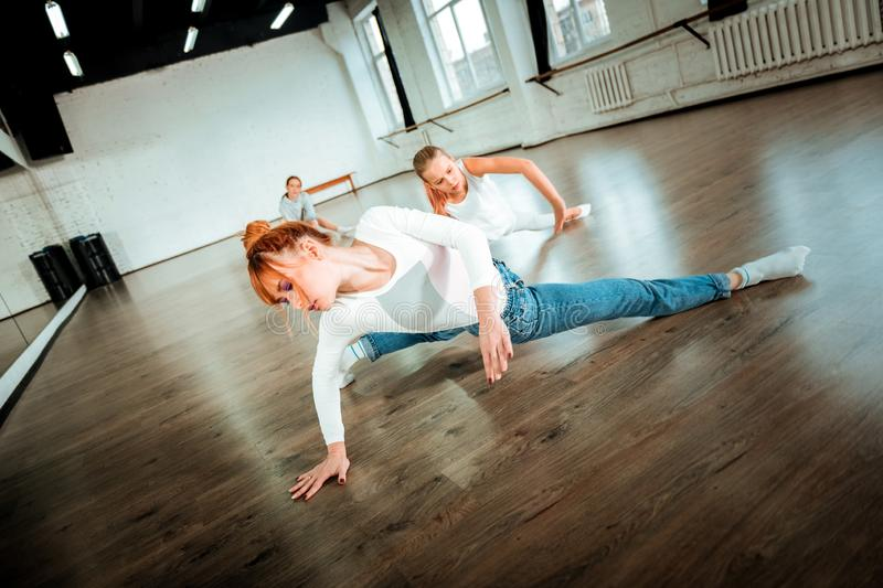 Professional ballet teacher and her student doing complicated dancing movements. Dancing workout. Professional ballet teacher and her student wearing white royalty free stock photography
