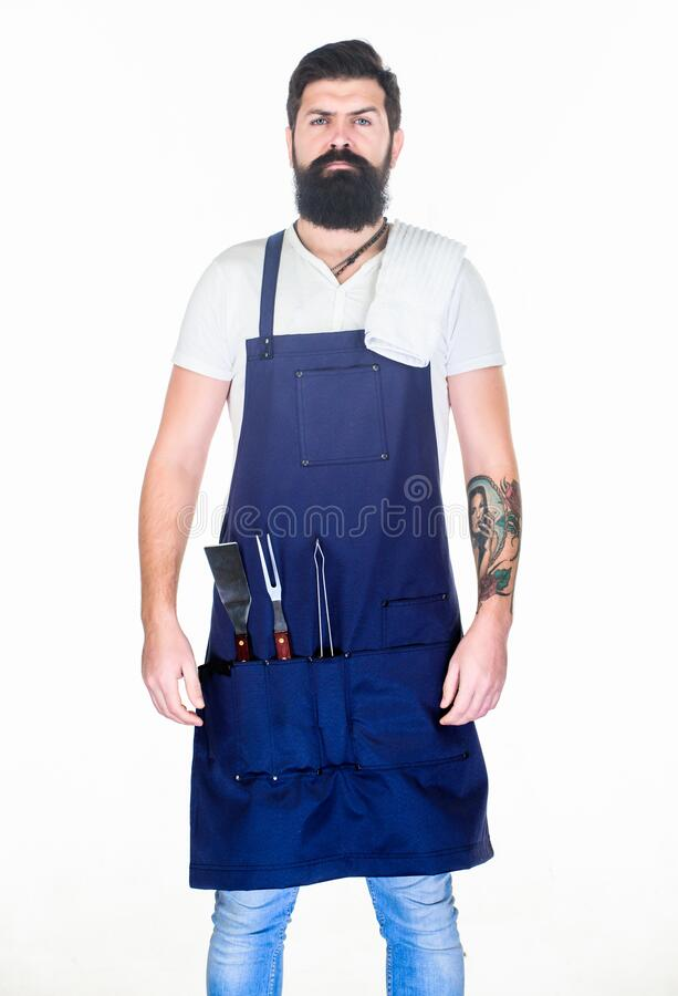 Professional barbecue utensil. Bearded hipster wear apron for barbecue. Roasting and grilling food. Tips cooking meat stock image