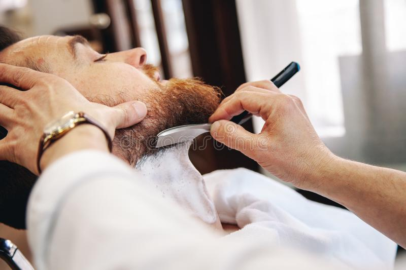 A barber shaves his client`s beard in the traditional way. royalty free stock photos