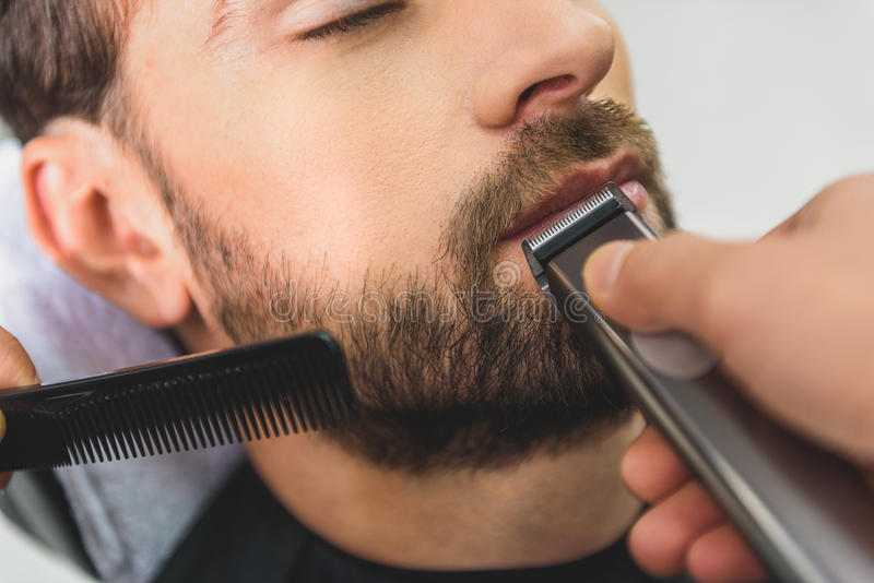 Professional barber using electric machine for haircut. Close up of hairdresser hands shaving male beard by clipper stock photo