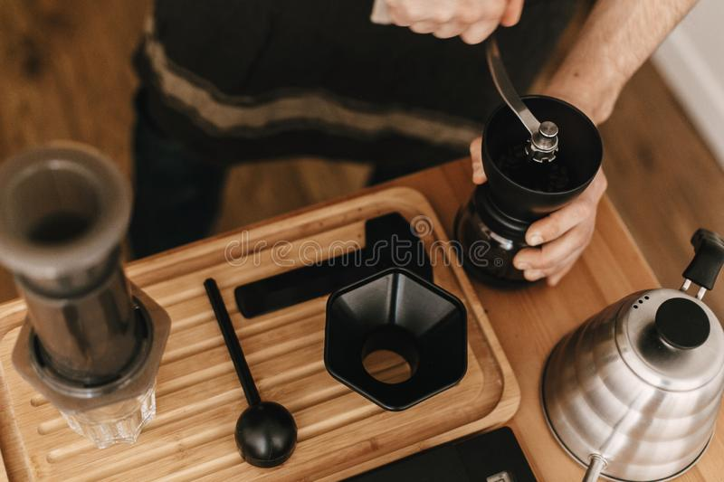 Professional barista grinding coffee for aeropress, alternative brewing method. Hands holding manual grinder and aeropress, scales stock images