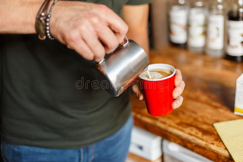 Professional barista man preparing coffee in a modern coffee shop. Male hands holding a metal cup and a paper red cup. Closeup. Of male hands and coffee royalty free stock image