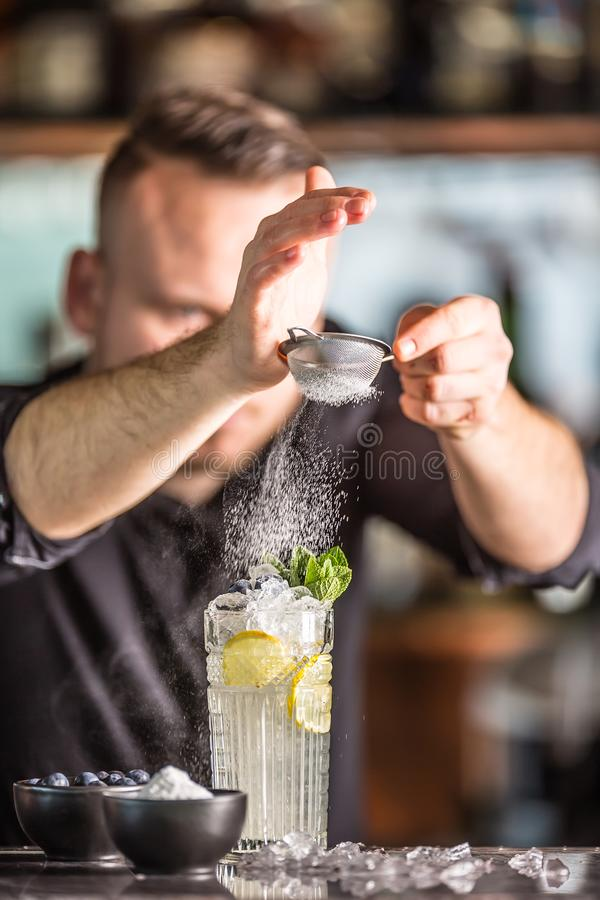 Professional barman making alcoholic cocktail drink with fruits sugar and herbs royalty free stock image