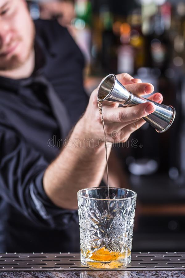 Professional barman making alcoholic cocktail drink old fashioned royalty free stock photography