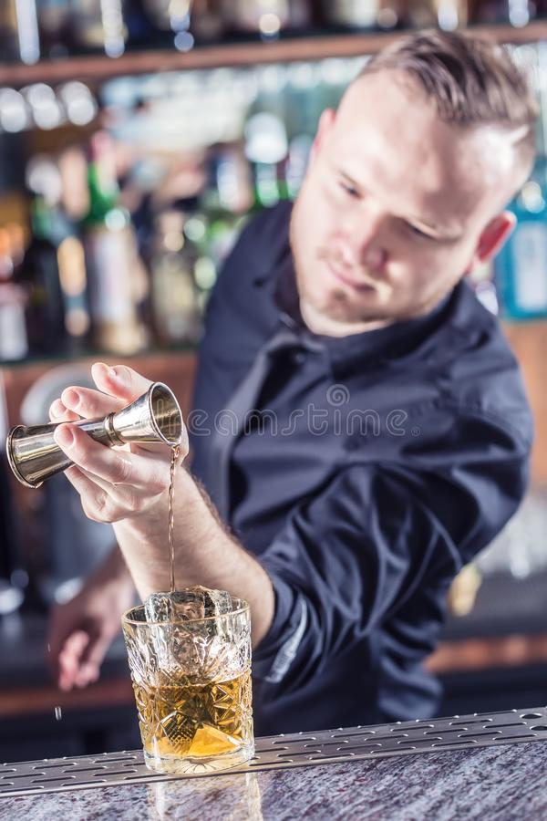 Professional barman making alcoholic cocktail drink old fashioned stock photography