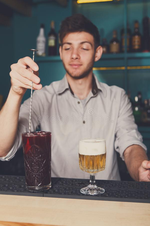 Young handsome barman pouring cocktail into glass royalty free stock image