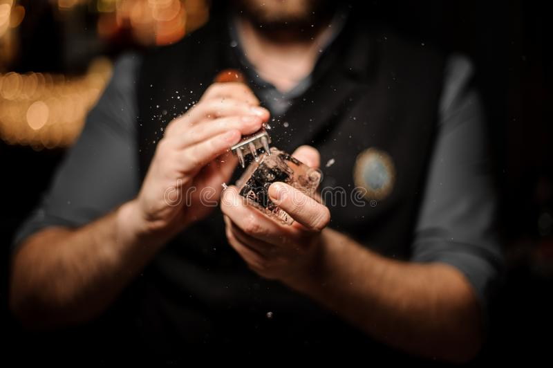 Professional bartender making an appropriate form to the ice cube with the special tool. On the bar counter on the blurred background stock photography