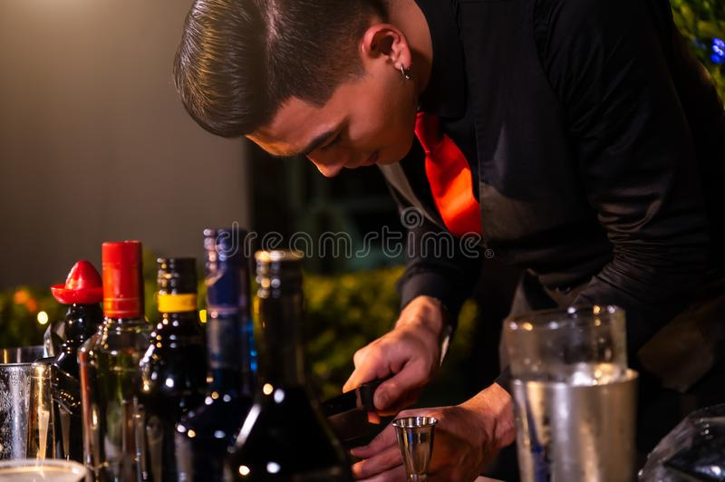 Professional bartender preparing fresh juice cocktail in drinking wine glass with ice at night bar clubbing counter. Occupation royalty free stock images