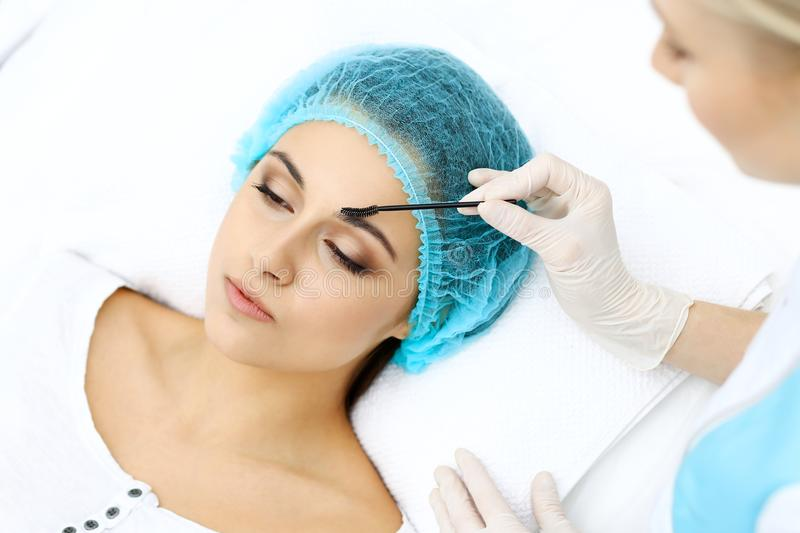 Professional beautician is doing cosmetic procedure at light medical background touching patient`s face with brush stock photos