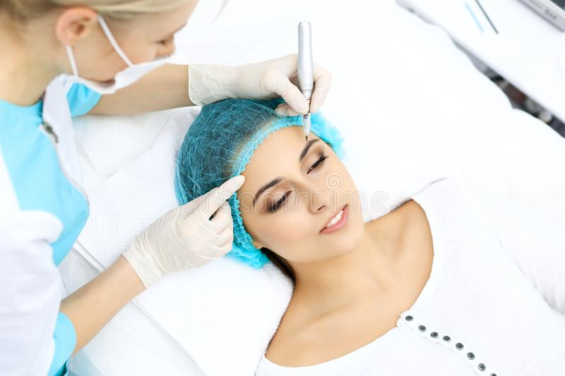 Professional beautician doing eyebrow tattoo at woman face. Permanent brow makeup in beauty salon, closeup. Cosmetolog. Professional beautician doing eyebrow royalty free stock images