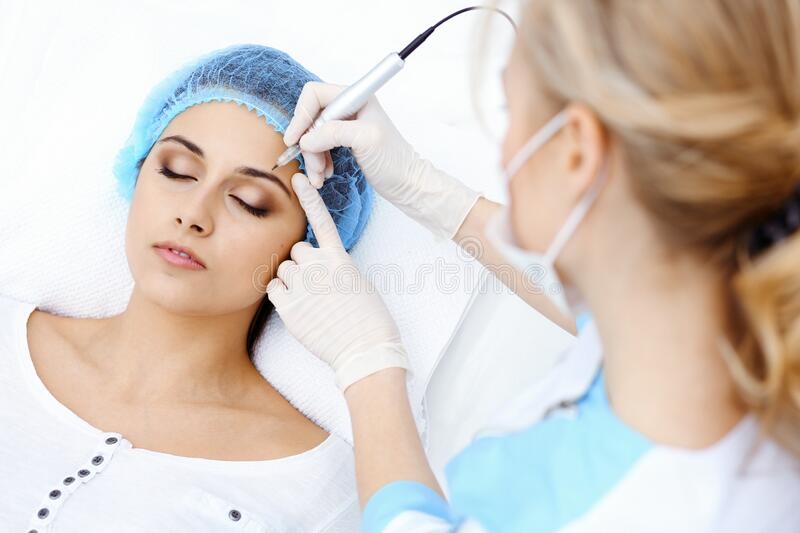 Professional beautician doing eyebrow tattoo at woman face. Permanent brow makeup in beauty salon, closeup. Cosmetology. Professional beautician doing eyebrow stock image