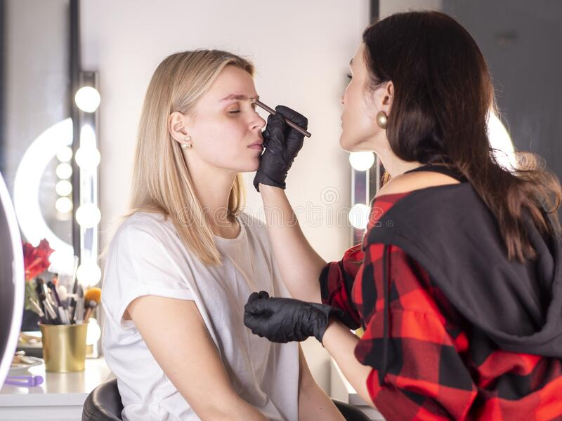 Professional beautician measuring the middle point of the eyebrows. Eyebrow shape correction.  royalty free stock photography