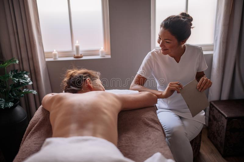 Professional beautician talking with female at beauty spa royalty free stock photo