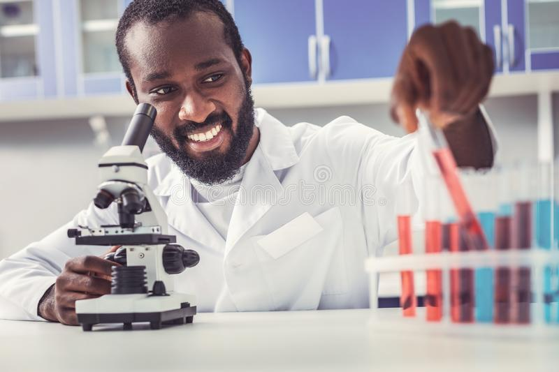 Professional bioengineer testing new vaccines. Professional bioengineer. Professional bioengineer testing new vaccines while sitting in laboratory wearing royalty free stock photos