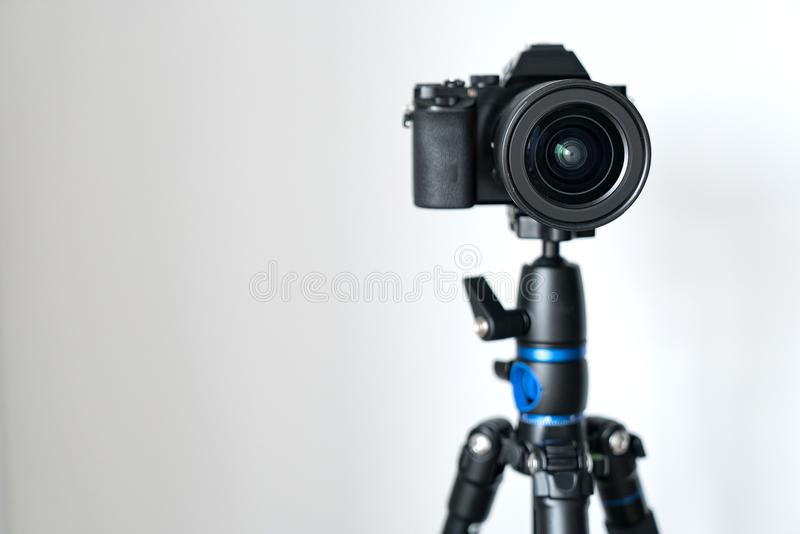 Professional black mirrorless camera stands on a tripod against a white wall. royalty free stock photography
