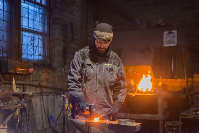 Blacksmith forging molten metal. Professional blacksmith forging molten metal on anvil at smithy, workshop. Handmade, craftsmanship and blacksmithing concept stock photo