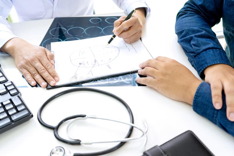 Professional brain doctor give a counselor to the patient. And tell the detail to help for good health, Stethoscope Medical instruments are on the table, advice stock photos