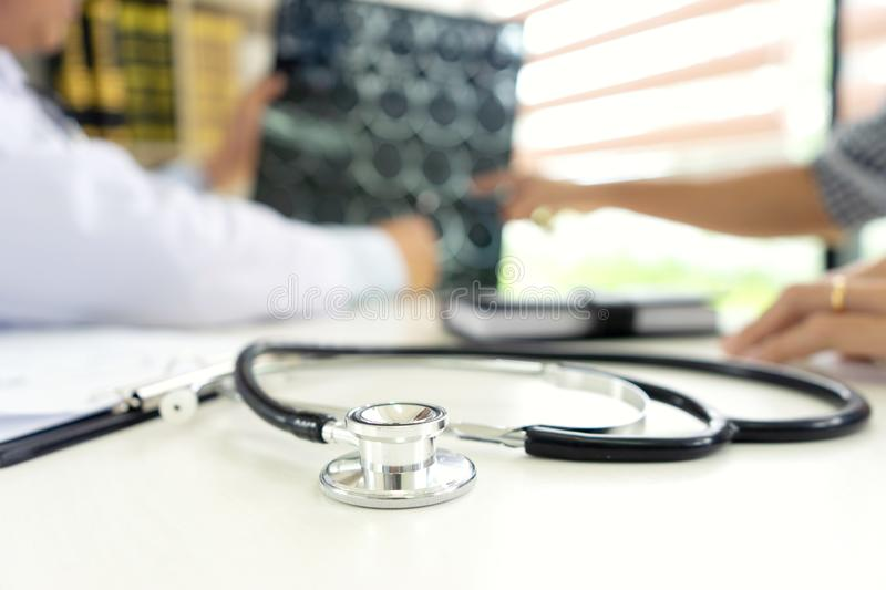 Professional brain doctor give a counselor to the patient. And tell the detail to help for good health, Stethoscope Medical instruments are on the table royalty free stock photo