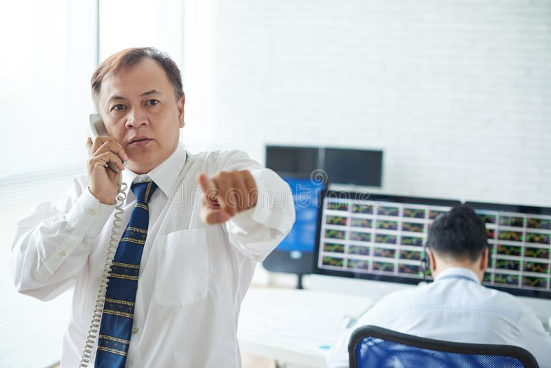 Professional broker. Professional experienced serious stock broker talking on phone and pointing at camera royalty free stock image