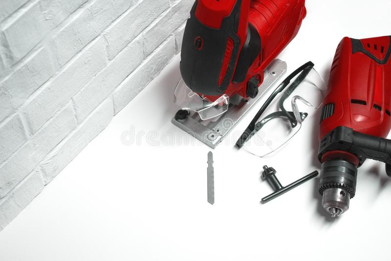 Professional building electrical tools for wood and metal. Electric jig saw and drill with safety glasses on a brick stock photography