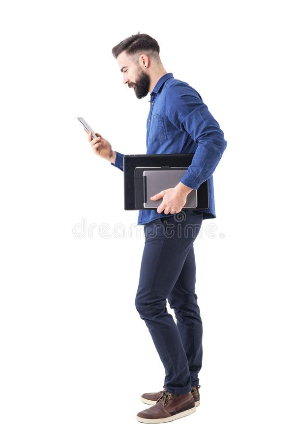 Professional business male executive checking phone carrying tablet and laptop under arm. Side view. royalty free stock image