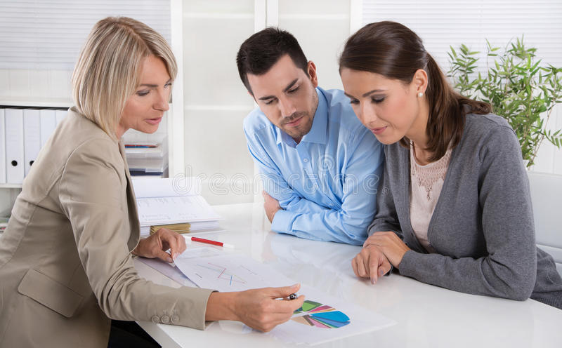 Professional business meeting: young couple as customers and an. Adviser for finance, retirement, investment or insurance royalty free stock image