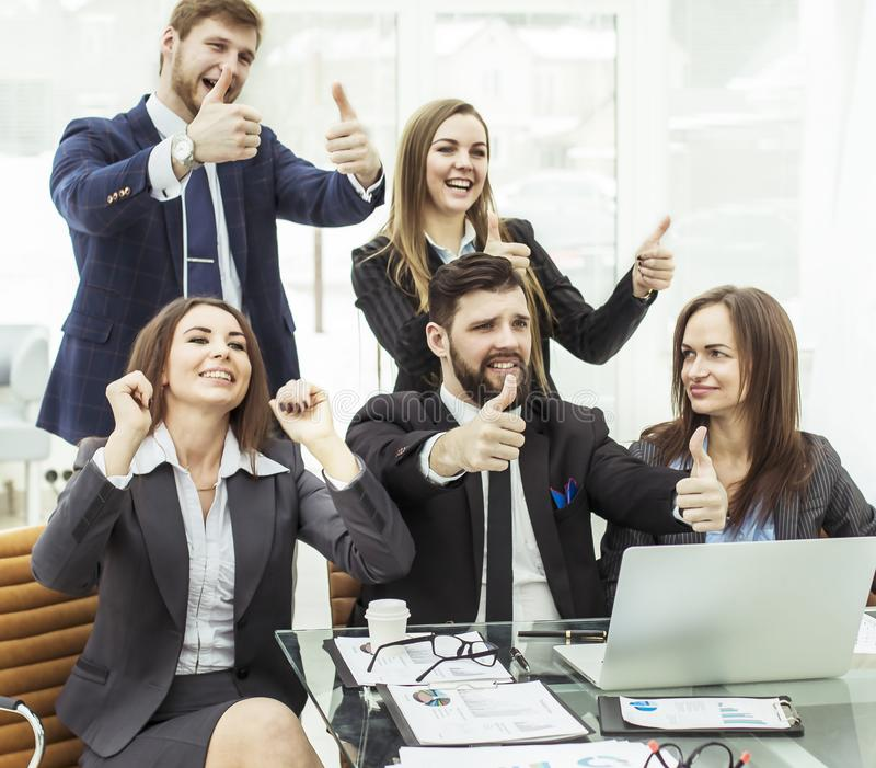 Success concept in business - friendly business team makes a gesture of thumbs up royalty free stock images