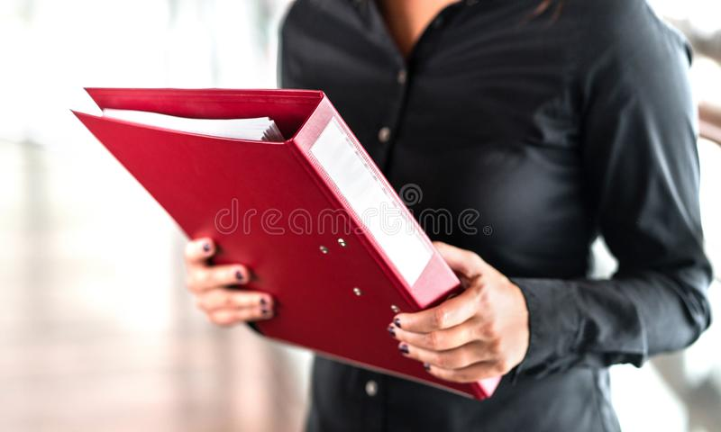 Professional business woman holding folder full of paper documents. stock image