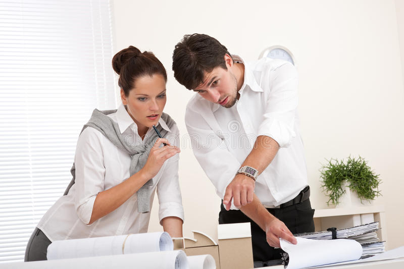 Professional businessman and businesswoman. At the office working together stock photo