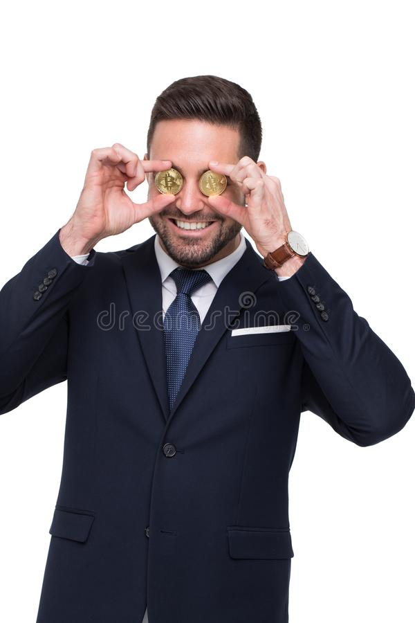 Professional businessman holding two golden bitcoin in front of royalty free stock image