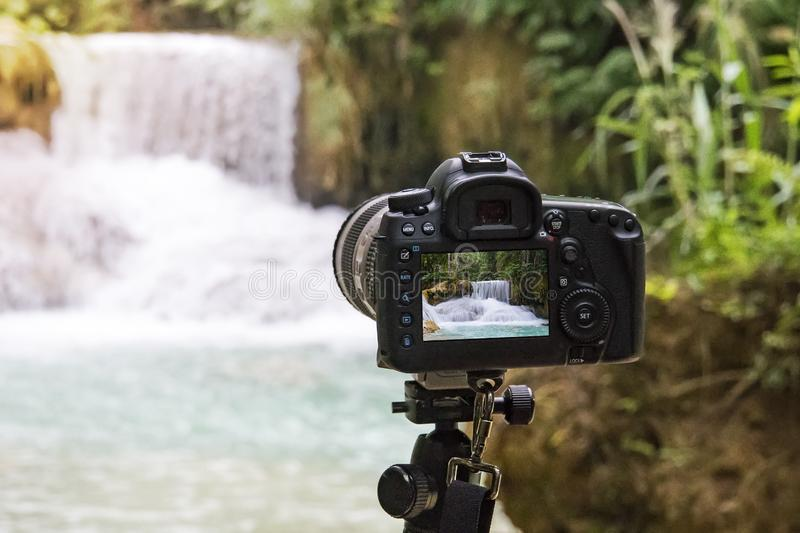 Professional camera photographing on a long exposure of a beautiful waterfall Kuang si in Laos. SLR camera on a tripod shooting a royalty free stock image