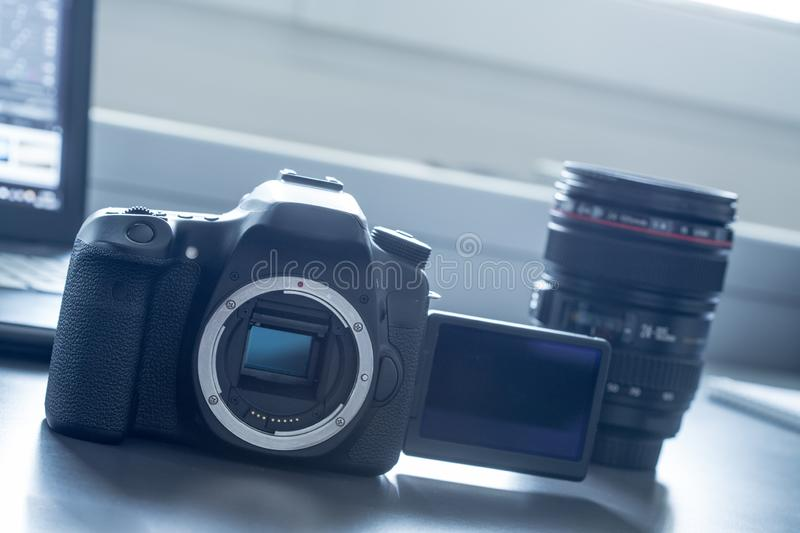 Professional camera: Reflex camera with open sensor. Lenses in the background. Professional reflex camera  with lsc screen on a table, camera sensor. Lenses in royalty free stock image