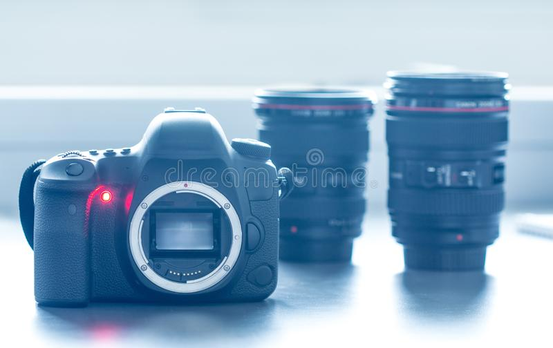 Professional camera: Reflex camera with open sensor. Lenses in the background. Professional reflex camera on a table, camera sensor. Lenses in the blurry stock photography