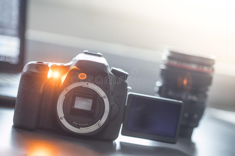 Professional camera: Reflex camera with open sensor. Lenses in the background. Professional reflex camera  with lsc screen on a table, camera sensor. Lenses in stock image
