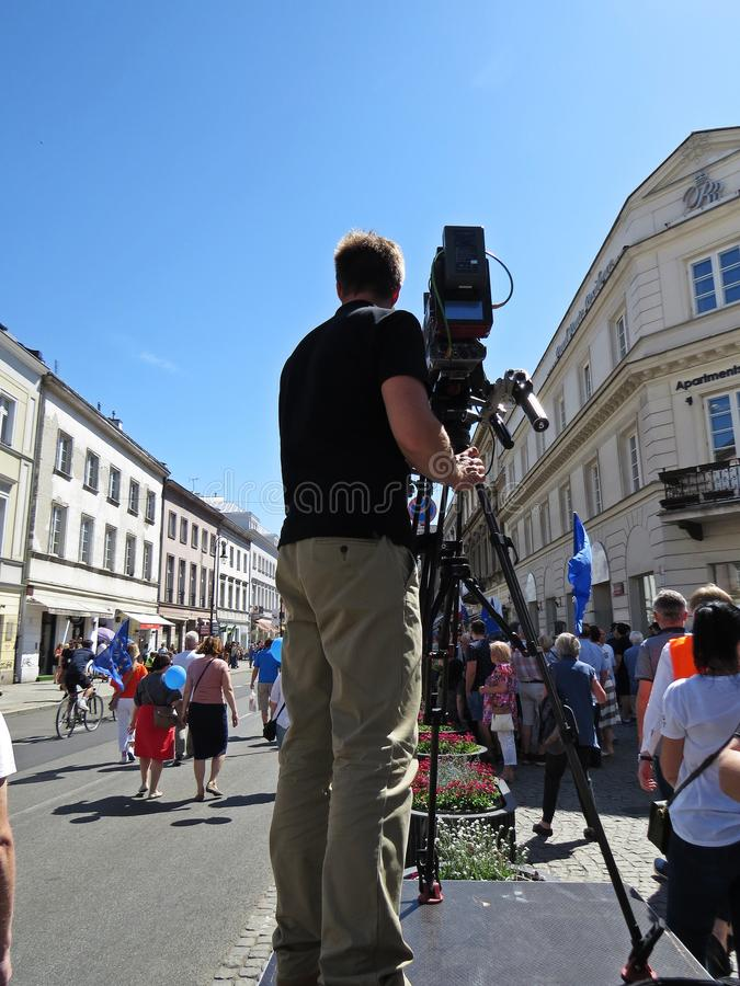 Professional Cameraman Filming and Broadcasting on Platform in City. Professional Cameraman Filming and Broadcasting on a Platform in City stock photography