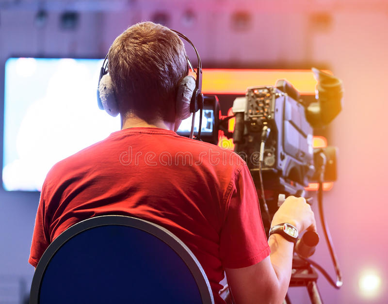 Professional cameraman. With headphones with HD camcorder in live television stock photo