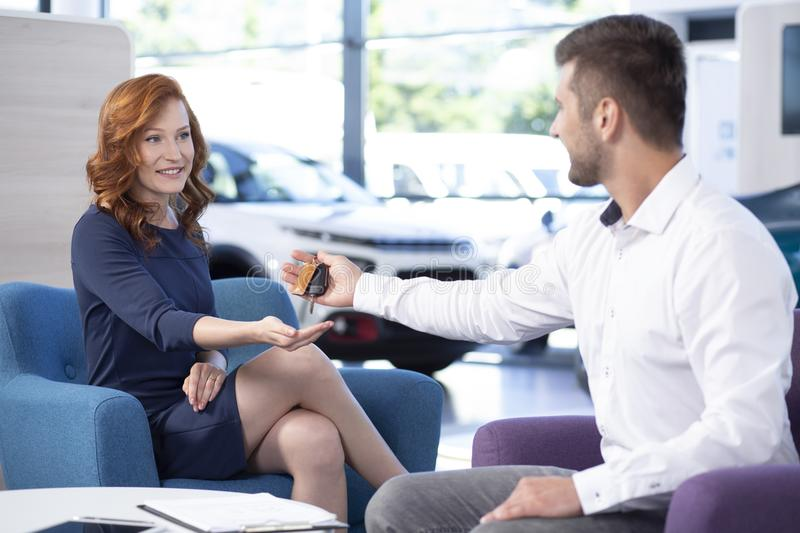 Professional car dealer giving keys to woman in exclusive salon with vehicles. Professional car dealer giving keys to women in exclusive salon with vehicles royalty free stock images