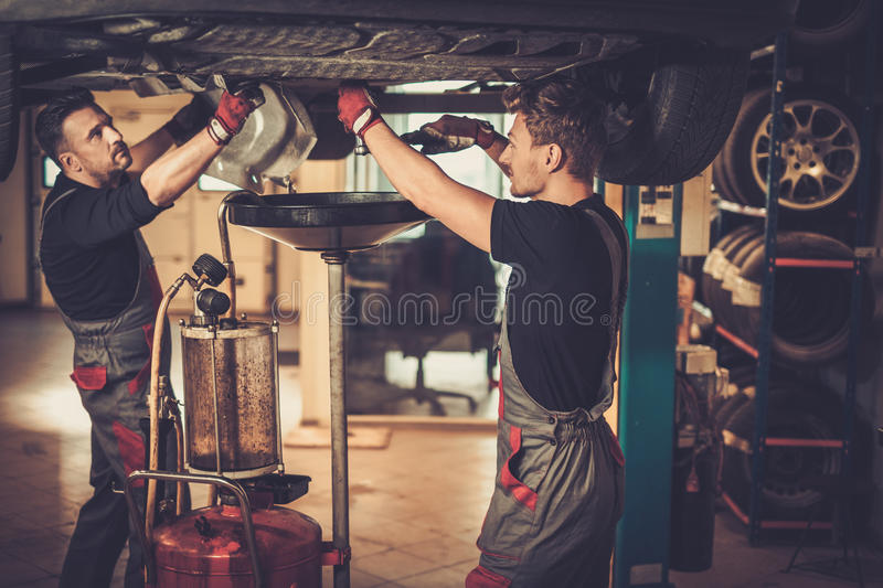 Professional car mechanic changing motor oil in automobile engi royalty free stock images