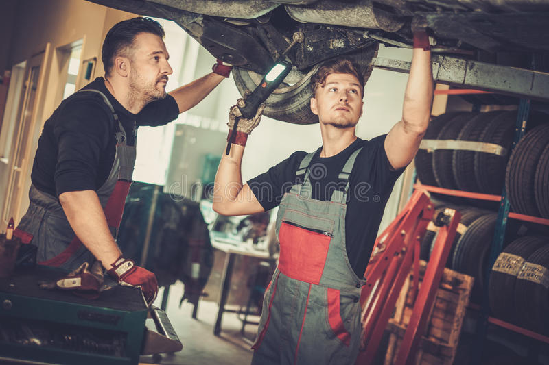 Professional car mechanics working under lifted car in auto repair service. stock images