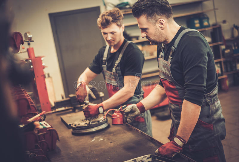 Professional car mechanics working at work table in auto repair Service. stock images