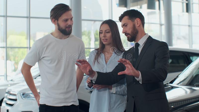 Professional car salesman is telling interested buyers beautiful couple about luxurious car in motor show while man and stock image