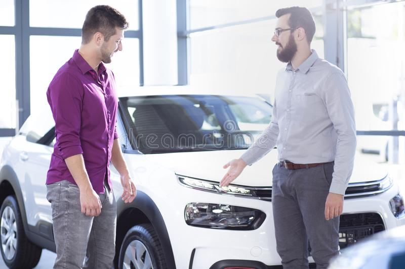 Professional car seller presenting exclusive vehicle to buyer in. The showroom concept royalty free stock photos