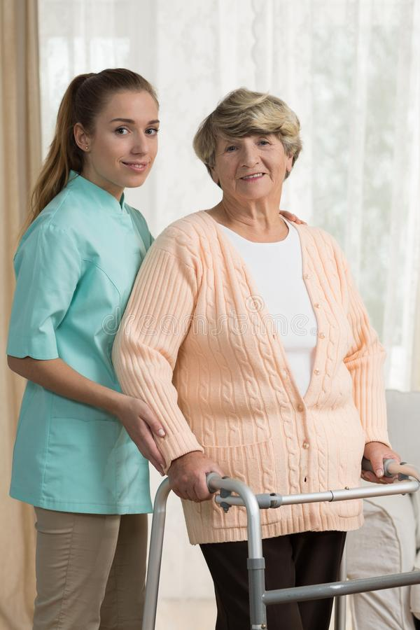 Professional carer helping old lady stock photo